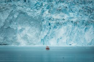 a-small-passenger-boat-in-front-of-the-huge-glacier-wall-at-the-eqi-glacier-in-greenland