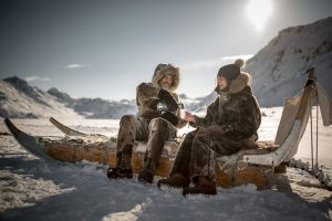 two-guests-on-a-dog-sled-trip-near-sisimiut-on-a-coffee-break-in-greenland